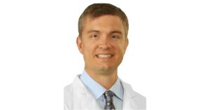 Caucasian Man Smiling in White Doctor Coat